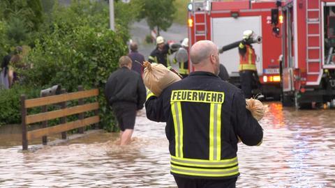 Ein Feuerwehrmann trägt einen Sandsack.