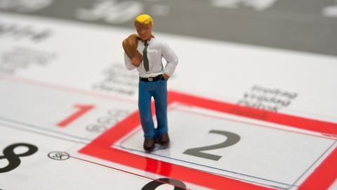 Brückentag - eine Spielzeugfigur steht auf einem Kalender