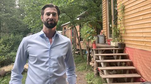 Der junge Bürgermeister Herz steht bei einem Besuch vor zwei Bauwägen aus Holz. Im Hintergund sind Bäume und Wald zu sehen.