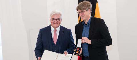 Bundespräsident Frank-Walter Steinmeier verleiht den Bundesverdienstorden an hr-Redakteur Andreas Dickerboom.