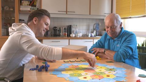 Spiele-Erfinder Klaus Teuber (rechts) spielt mit seinem Sohn das Spiel Catan