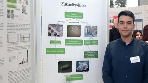 "Christos Assiklaris, Teilnehmer bei ""Jugend forscht"", vor einer Schautafel"