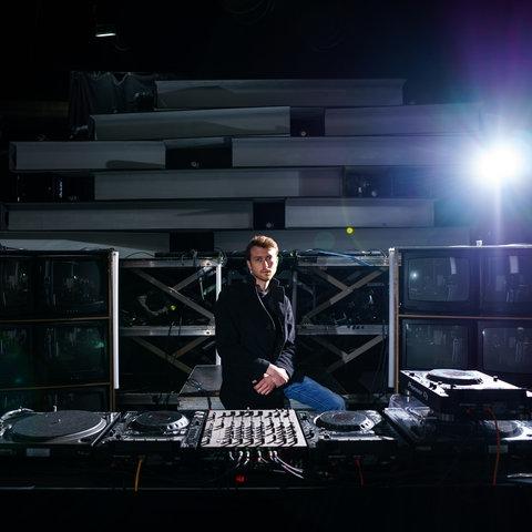 """Victor Oswalt steht hinter dem DJ-Pult im leeren Club """"Tanzhaus West"""" in Frankfurt."""