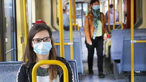 Eine Frau sitzt mit Mund-Nase-Schutz in einer Straßenbahn