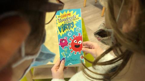 """Kinder halten den Corona-Comic """"Das geheime Tagebuch eines miesen Virus"""" in Händen"""