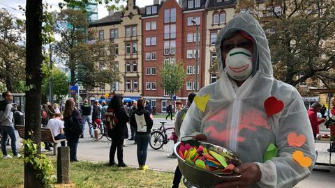 Ein Teilnehmer in einem weißen Schutzanzug und mit Gesichtsmaske verteilt auf dem Bebel-Platz in Kassel bunte Papierherzen.