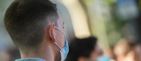 Ein junger Mann trägt eine Mund-Nase-Bedeckung