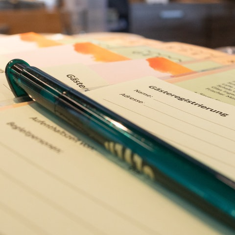 Zettel für die Gästeregistrierung liegen im Vordergrund auf einem Tisch in einem Café. Im Hintergrund ist - unscharf - die Bar und der Barmann zu sehen.