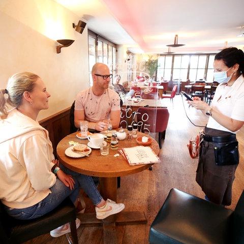 Eine Kellnerin bedient zwei Gäste in einem Café.