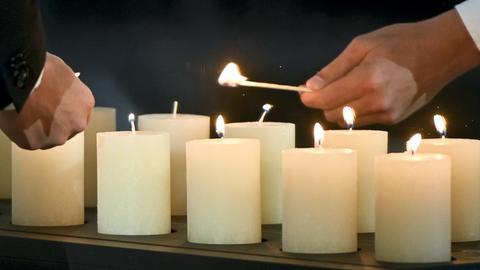 Angehörige von Corona-Toten zünden Kerzen zum Gedenken an