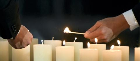 Viele brenndene weiße Kerzen. Zwei Hände in Großaufnahme mit Streichhölzern, welche die Kerzen anzünden.