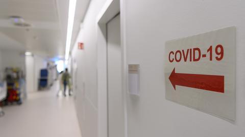 """Ein Schild mit einem Richtungspfeil und der Aufschrift """"Covid-19"""" Bereich klebt in einem Klinikflur an der Wand."""