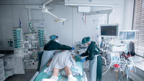 Zwei Ärzte stehen um ein Krankenbett einer Intensivstation.