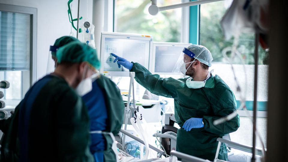 Drei Ärzte stehen um ein Krankenbett einer Intensivstation.