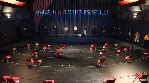 """Foto eines Innenraumes eines Theaters. Vereinzelte Stühle stehen im sonst voll gestellten Publikumsraum. Auf dem Vorhang steht: """"Ohne Kunst (und uns) wird es still."""""""