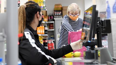 Im Supermarkt: Eine Kundin reicht der Kassiererin die Lebensmittel entgegen, beide tragen eine Maske.