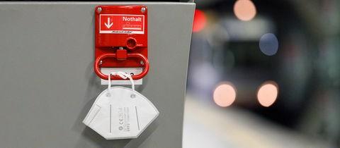An einer Notbremse in einer Bahnhaltestelle hängt eine FFP2-Maske.