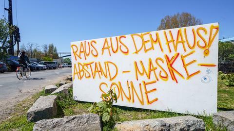 """Ein handgemaltes Schild am Offenbacher Hafen fordert seine Betrachter auf: """"Raus aus dem Haus! Abstand - Maske - Sonne"""""""