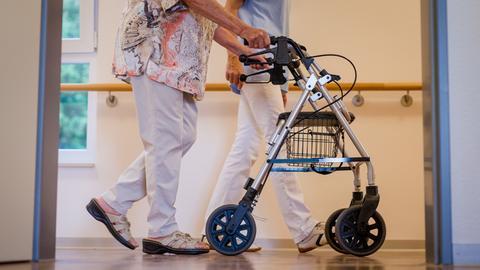 Im Vordergrund schiebt eine ältere Frau ihren Rollator durch einen Pflegeheim-Korridor. Im Hintergrund ist zu erkennen, dass sie von einer Pflegerin in einem blauen Kittel begleitet wird.