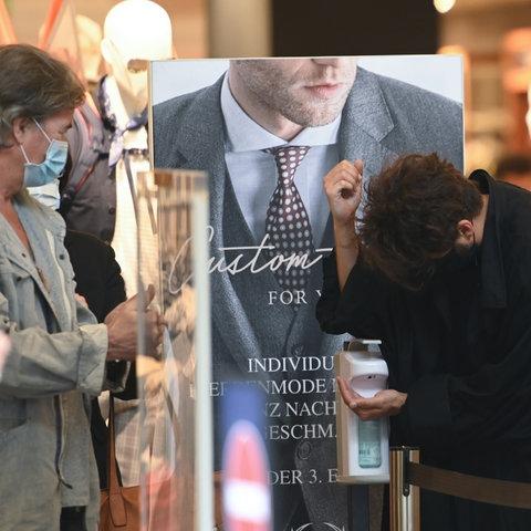 Kunden desinfizieren ihre Hände am Eingang eines Textilgeschäfts auf der Frankfurter Zeil.