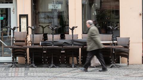 Ein älterer Mann mit Glatze und Brille eilt an einem geschlossenen Lokal in Wiesbaden vorbei. Vor der Gaststätte sind Tische und Stühle zusammengeräumt und angekettet.