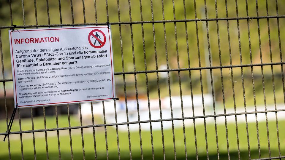 Zu sehen ist ein Schild an einem Zaun, das auf die Schließung eines Spielplatzes wegen des Coronavirus hinweist.