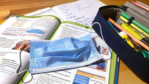 Ein fotografischer Blick auf den Schreibtisch eines Schülers. Zwischen den Arbeitsmaterialien liegt eine OP-Maske.
