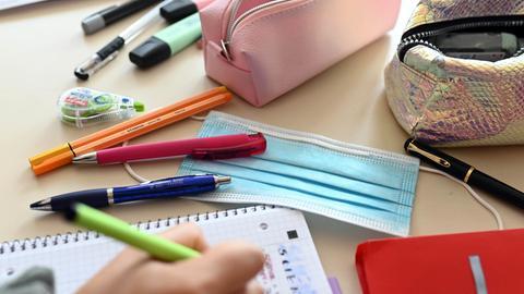 Ein fotografischer Blick auf den Schreibtisch einer Schülerin. Zwischen den Arbeitsmaterialien liegt eine OP-Maske.