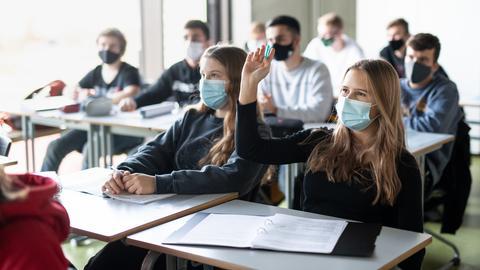 Schülerinnen und Schüler sitzen mit Masken im Unterricht