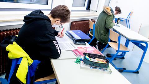 Schüler eines geteilten Kurses der Oberstufe sitzt mit Mund-Nasen-Bedeckung in einem Klassenraum und bearbeitet eine Aufgabe.