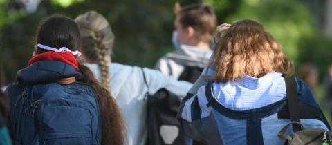 Schülerinnen und Schüler von hinten mit ihren Schultaschen.