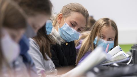 Schülerinnen tragen im Klassenzimmer eine Alltagsmaske