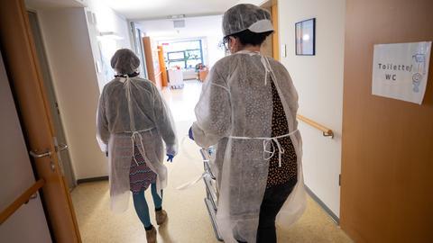 Foto aus einem Seniorenheim. In Schutzkleider gehülltes Pflegepersonal versorgt die Bewohnerinnen und Bewohner.