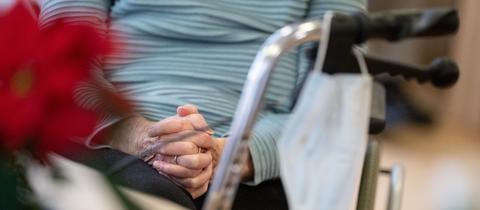 Foto aus einem Seniorenheim. Zu sehen ist sind betende Hände einer im Rollstuhl sitzenden Person. Am Rollstuhl hängt eine OP-Maske. Daneben steht eine Weihnachtsstern-Pflanze.