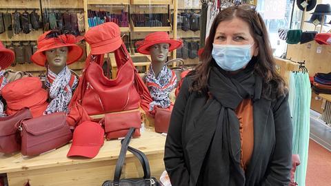 Foto einer Verkäuferin in einem Hutladen. Neben und hinter ihr sind viele Hüte, Taschen und Handschuhe zu sehen - vor allem in der Farbe Rot.