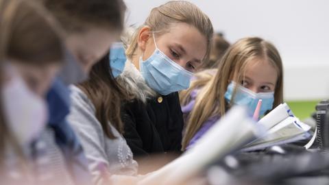 Schülerinnen und Schüler einer 5. Klasse eines Frankfurter Gymnasiums mit Mundschutz im Unterricht.