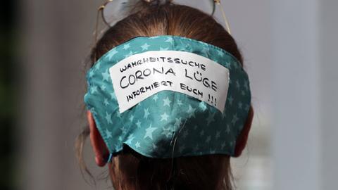 """Frau bei einer Demonstration mit Maske mit Aufschrift """"Wahrheitssuche - Corona-Lüge - informiert euch"""""""
