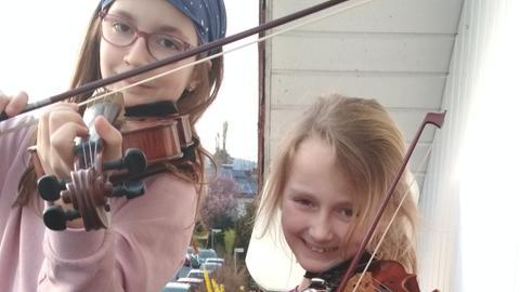Die beiden Töchter der Familie Joch aus Eschborn beim abendlichen Musizieren auf dem Balkon
