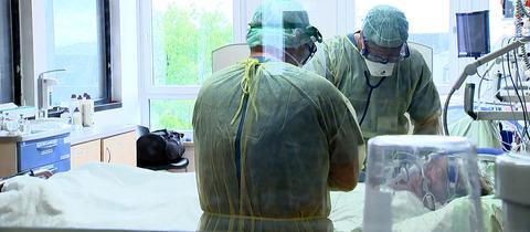 Arzt Hendrik Halfar (rechts) und Krankenpfleger Markus Dienst bei der Behandlung eines Covid-19-Patienten im Uniklinikum Gießen
