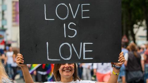 """Viel Liebe: Eine Teilnehmerin trägt ein Schild mit """"Love is Love"""" durch die Straßen von Frankfurt."""