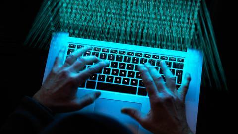Foto von zwei Händen an einem Laptop, auf dessen Bildschirm viele O-en und 1-en leuchten.
