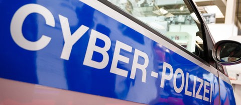 """Foto des Schriftzuges """"CYBER-POLZEI"""" auf einem Polizei-Auto."""
