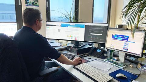 """Foto eines """"Cyber-Polizisten"""" bei der Arbeit an seinem Schreibtisch mit vielen Bildschirmen."""