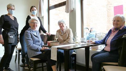 Drei sitzende und zwei stehende Frauen in Büdingen in einem Café.