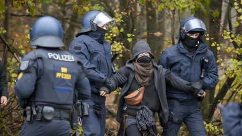 Polizisten bringen eine Besetzerin aus dem Wald.