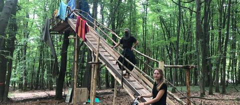 Zwei junge Menschen im Wald vor einem Baumhaus