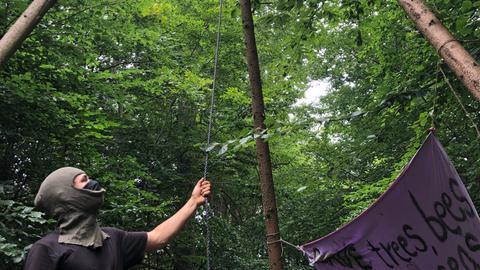 Ein vermummter junger Mann zeigt auf ein Gestell aus drei Baumstämmen
