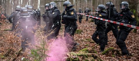 Polizisten sichern den Rand einer Rodungsschneise, als Demonstranten versuchen, die Polizeiabsperrung zu durchbrechen. Im Vordergrund brennt ein von Aktivisten geworfener Rauchtopf.