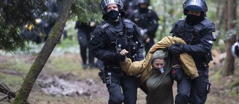 Eine Aktivistin wird von der Polizei in Gewahrsam genommen.