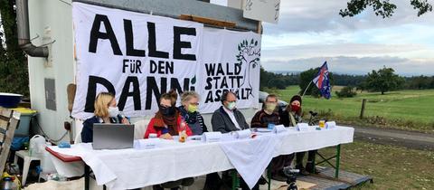 Sechs Menschen, die im freien an einem großen Tisch sitzen, umgeben von Protestplakaten